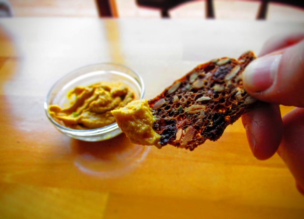 winter squash hummus dip on a rosemary raisin nut cracker