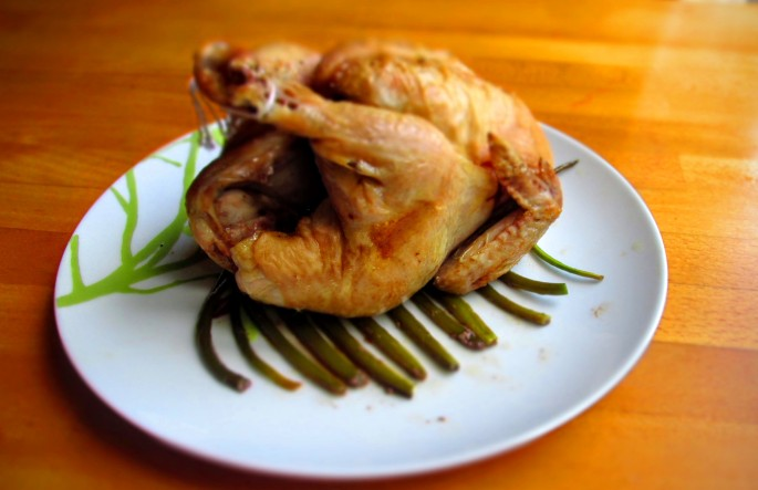 roast cornish game hen on a raft of scapes
